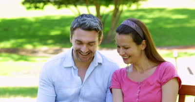 stock-footage-happy-couple-sitting-on-a-park-bench-using-tablet-pc-on-a-sunny-day